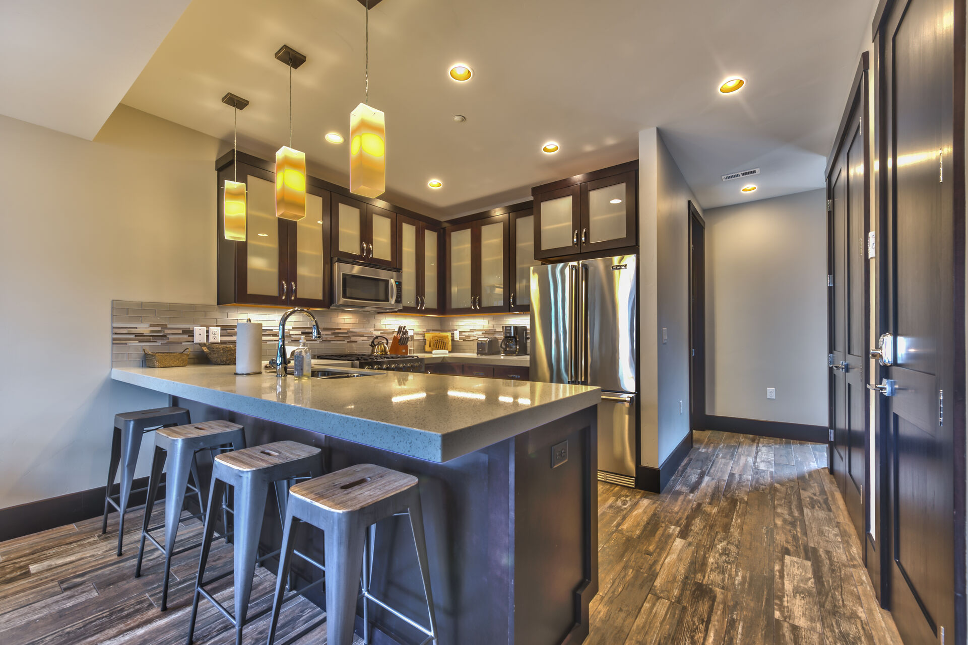 Fully Equipped Kitchen with Stainless Steel Appliances, a 6-Burner Viking Gas Range, Granite Countertops, Bar Seating for 4, and adjoining Dining Area