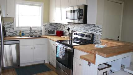 The updated kitchen features a tile backsplash, bar seating and butcher block counters.