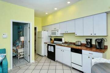 Living space with large HDTV, kitchen, dining area