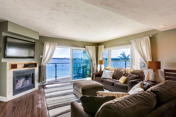 Sofas, Ottoman, Side Tables, TV, Fireplace, and Windows with Panoramic Bay Views.