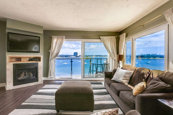 Sofa, Ottoman, Fireplace, TV, and Multiple Windows with Panoramic Bay Views.
