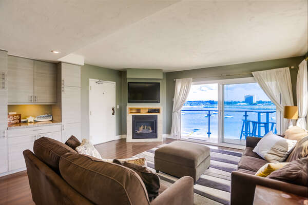 Sofas, Ottoman, Wall Cabinets, TV, Fireplace, and Windows with Panoramic Bay Views.