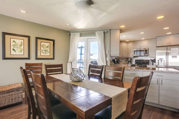 Dining Table, Chairs, Ceiling Fan, and the Kitchen with Countertop Bar.