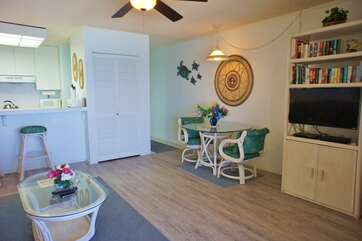 Dining table, chairs, smart TV, ceiling fan, and breakfast bar