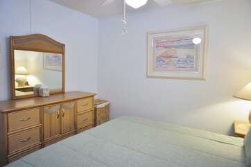 Bedroom with dresser, mirror, large bed, and ceiling fan