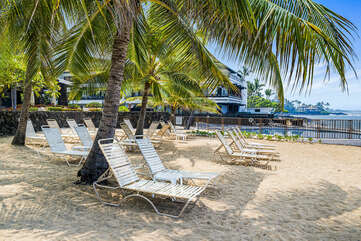 Oceanfront seating under palm trees.