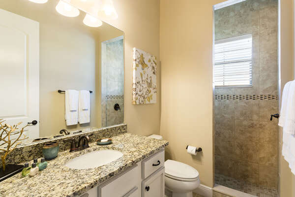 The bathroom off of the king room has granite counter tops and shower with tile surround