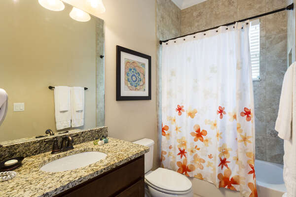 The bathroom off of the queen room has a tub shower combination with tile surround