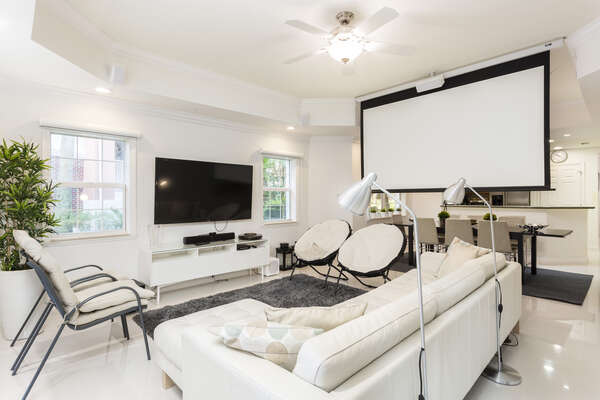Living room includes projector with pull-down screen.