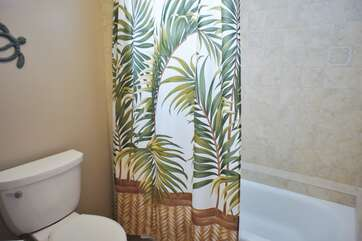 Master Bathroom tub and toilet with tropical shower curtain