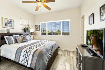 Bedroom with Large Bed, Dresser, Smart TV, and Ceiling Fan