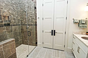 The en suite bathroom has a granite topped sink, and a large tiled walk in shower.