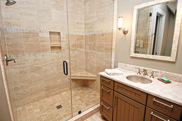 The adjoining bath has a large tile shower and two granite topped vanities.