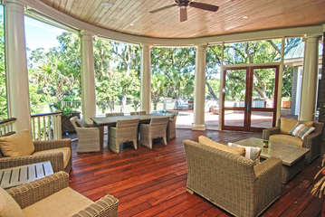 Spacious screened in porch off the living area overlooks the pool and large deck.