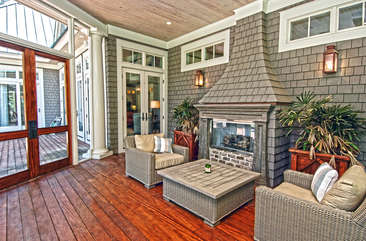 The large screened porch has a gas fireplace, dining table, and large HD TV with streaming function.