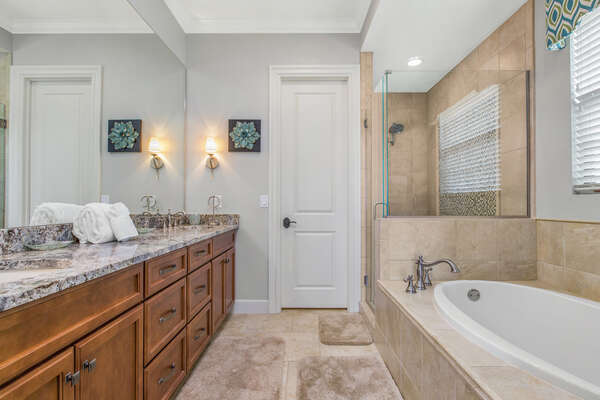 The en-suite bathroom features a glass shower and soaking tub