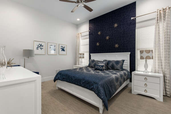 Calming navy and grey master bedroom with a king bed located on the ground floor
