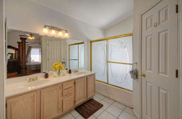 Dual vanity sinks, tub/shower combination and walk-in closet in primary bath