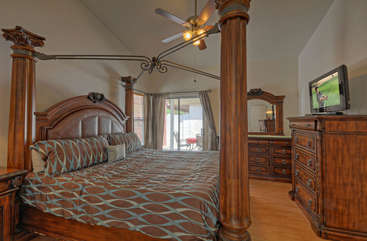 Gorgeous king size canopy bed in primary bedroom with patio access