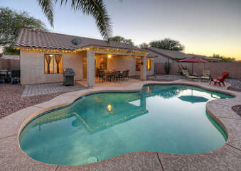 Landscaped backyard has a lovely covered patio plus pool deck seating.