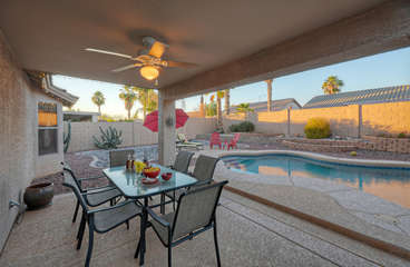 Covered patio has a view of the lagoon style pool and is furnished for outdoor dining.
