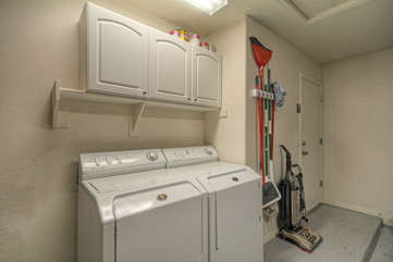 Laundry room has family size appliances and detergent is stocked.