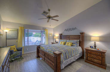Primary bedroom has beautiful king bed and appreciative outdoor view