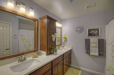 Primary bath has dual vanity sinks and a large walk in shower