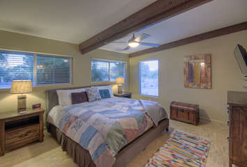 Stylish west primary suite includes a king bed, exposed beam and large windows