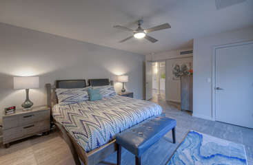 The east primary suite is at the opposite end from the west suite and features a king bed, TV, ceiling fan, private bath and a walk-in closet.