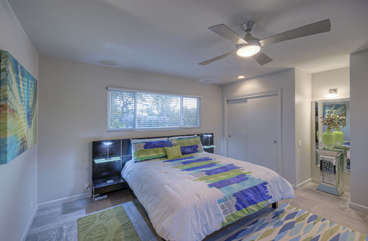 Bold and colorful west primary suite features a king bed, TV, ceiling fan, private bath and two closets.