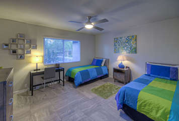 Trendy third bedroom has a queen and full size bunk beds, TV, desk and ceiling fan.