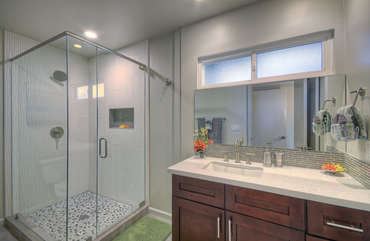 The west primary bath has a modern glass and tile walk-in shower.