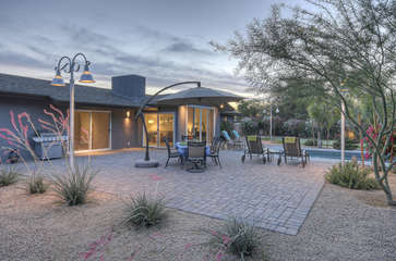 Large back patio has a gas grill, dining furniture and comfy chaises for enjoying the great outdoor setting.