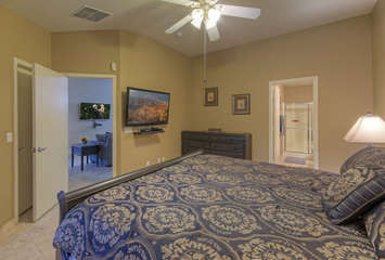 Divine primary suite with appealing decor includes a king bed, walk-in closet and TV