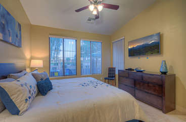 First floor master suite includes a golf course vista and has a large television for guests who prefer watching their favorite programs in more secluded location