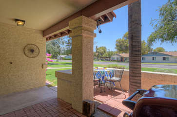 Furniture and gas grill on covered patio invite you to dine outdoors in warm and sunny weather.