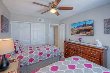 The second bedroom has new decor that includes two extended length twin beds, a ceiling fan and a large TV