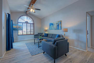 Great room has exposed beam, large arched window, stylish updated decor and a Smart TV for streaming