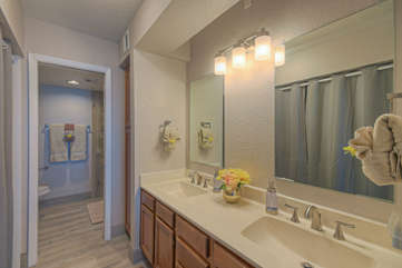 The remodeled primary bath has 2 vanity sinks and new light fixtures