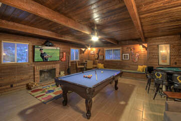 Rustic game room has pool and card tables, TV and a wood burning fireplace. A queen bed can be added to make this the 5th bedroom.