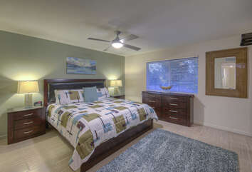 Primary suite has deluxe king bed, ceiling fan and TV