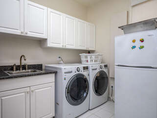 The laundry room features a front load washer (HE)/dryer and extra refrigerator.