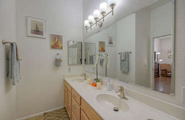 Primary bath features a large, well-lit vanity with dual sinks.