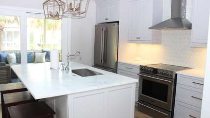 Special details in the kitchen includes a soft blue ceiling and steel range hood.