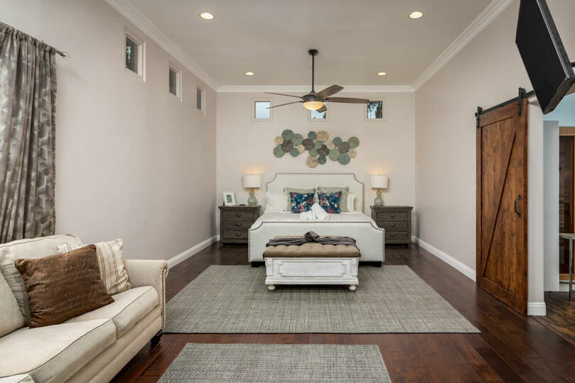 Comfortable primary bedroom with nightstand, love seat, TV, and a private bathroom with barn doors