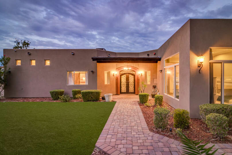 Secluded front patio with lawn and hidden entryway