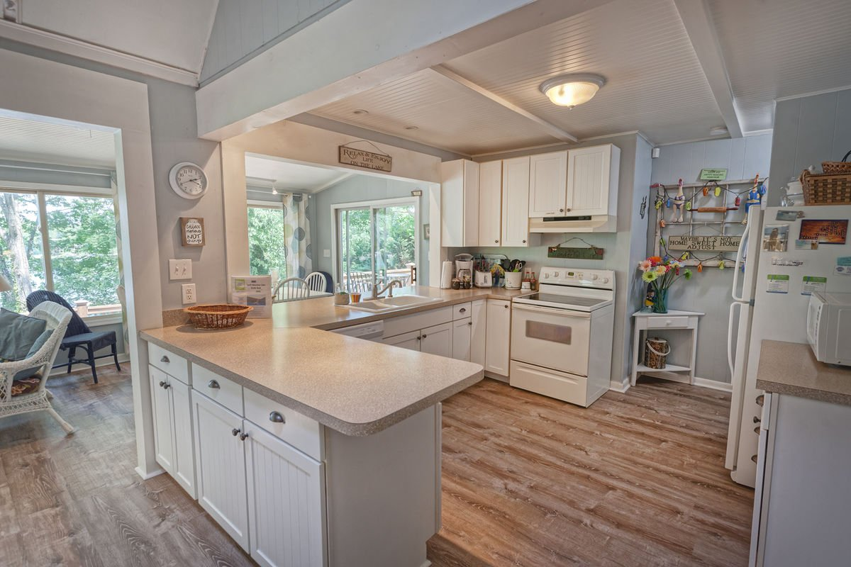 Kitchen in a square shaped room, with ample counter space and modern appliances.