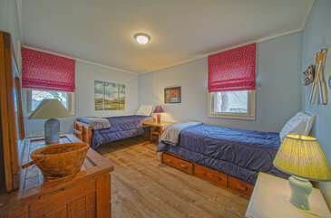 Two beds in bedroom 4, with nightstands and lamps.