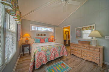 Bedroom 2 with large, colorful bed and dresser.